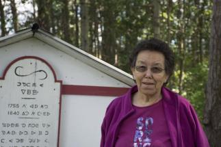 Elder Lillian Sam in front of Kw'eh's Grave
